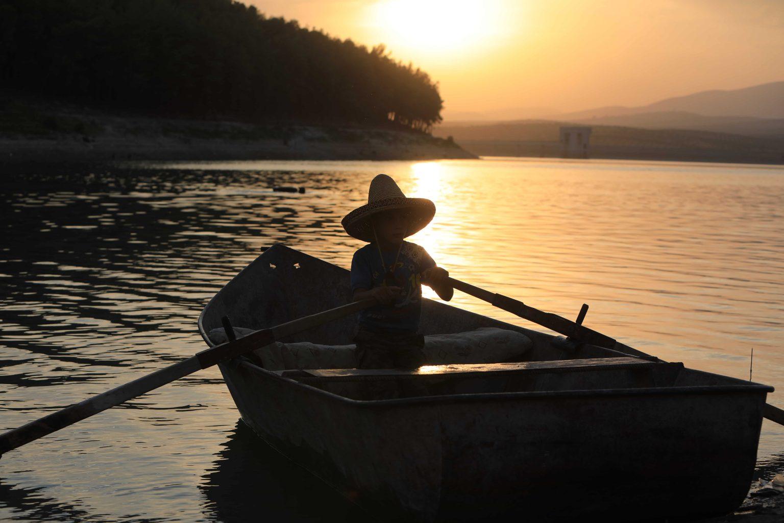 بالصور الطفل السوري مالك يجدف بقارب قديم من أجل حياة كريمة